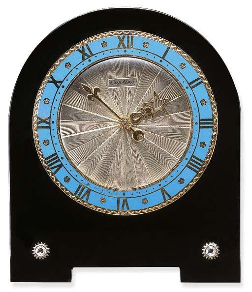 AN ART DECO ENAMEL, BLACK ONYX AND DIAMOND DESK CLOCK, BY CARTIER