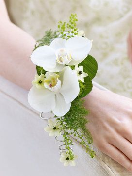 Rich in exquisite detail, this stunning wrist corsage is a beautiful style statement. Two exotic white orchids are complemented with perfect little ornithogalum flowers, deep green leaves and delicate fern.
