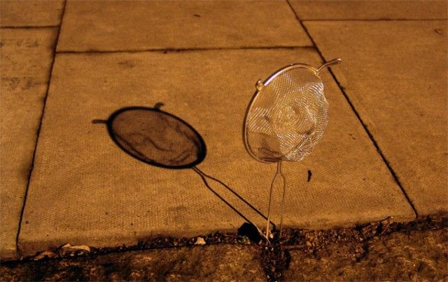 Back in 2009, artist Isaac Cordal shaped wire mesh kitchen colanders into faces and installed them on the streets of London, where street lights cast shadows of the faces on to foot paths.