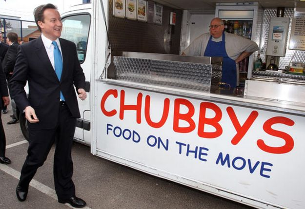 With suit jacket straining, David Cameron ambled past a food van in a timber yard in Reading. Incredibly Awkward Pictures Of Politicians Standing In Front Of Unfortunate Signs
