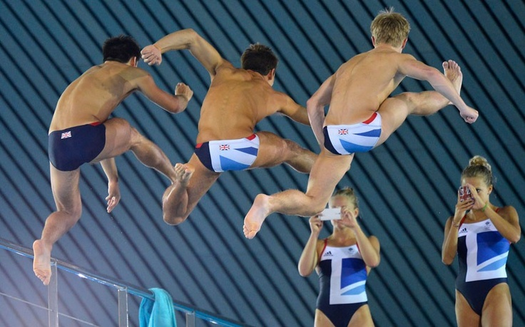 British divers Tonia Couch and Sarah Barrow take photographs of Tom Daley  and  teammates jumping from the 10 metre board at the Aquatics Centre