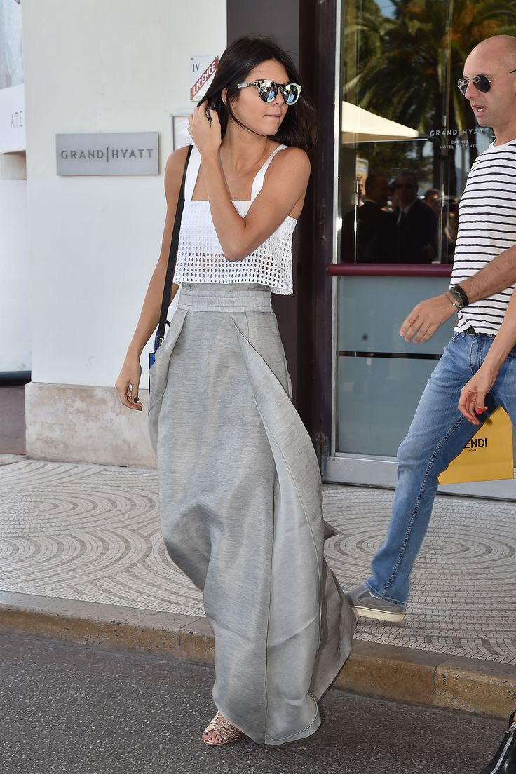 In a white eyelet crop top, Sally LaPointe skirt, and strappy gold sandals.