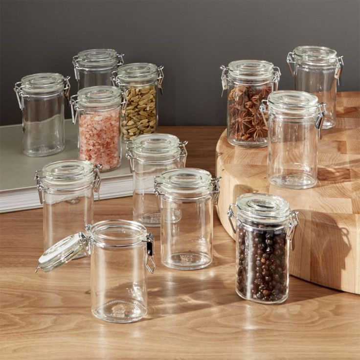 Shop Mini Oval Spice-Herb Jars with Clamp Set of 12.  A cool commercial look for herb and spice storage.  Clean glass oval mini-canisters clamp down on contents with tight-sealing gaskets and sleek chrome closures.
