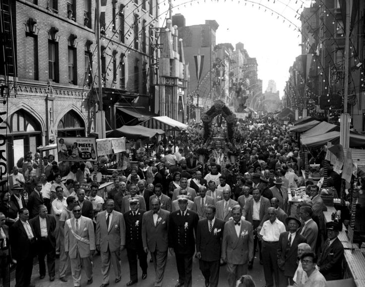 The 26th anniversary of the Feast of San Gennaro, an annual 11-day religious festival in Little Italy featuring parades, food and music, is observed with merry-making on Mulberry St in 1951. In attendance are Deputy Fire Chief Leopold Rossi, Postmaster George Bragalini and Fire Chief Peter Loftus.