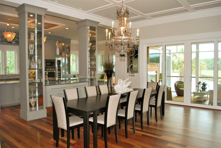 Dual glass display cases separate dining room from kitchen. Large white and black crystal chandelier hangs above black table for ten. Glass doors lead into sunroom.