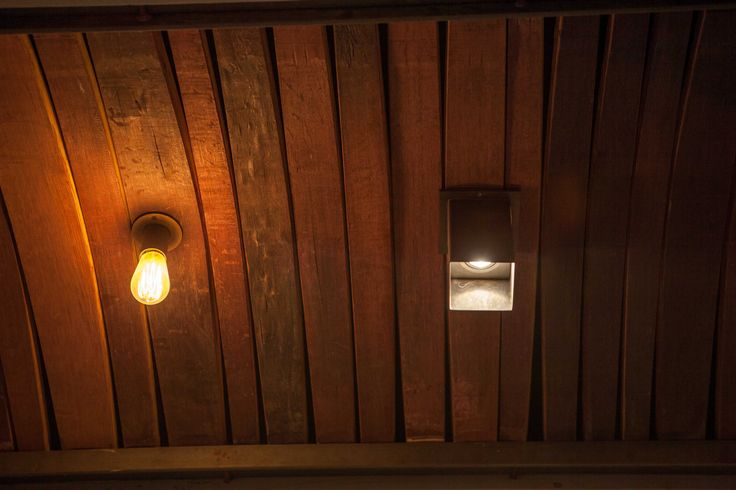 Ceiling lights fitted against reclaimed red wine barrel planks