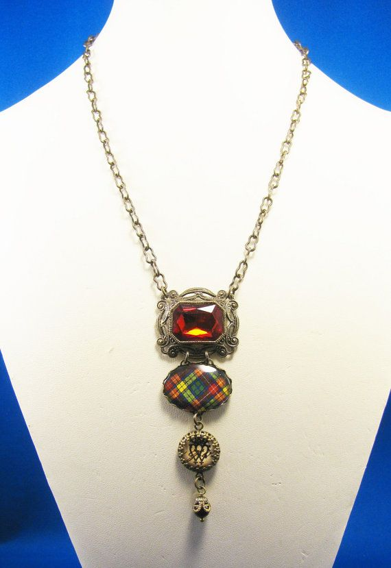 This necklace was created by me as part of my Ancient Romance Series, the Scottish and Irish Tartans Collections. It is from my new mini collection of tartans all dressed up for special occasions such as a special St. Patricks Day dinner dance or formal party. It features one of my most often-requested tartans, gorgeously complex Buchanan clan tartan in red, yellow, blue and green.  I framed the tartan under glass in a 25x18mm lacy bezel setting and enhanced it with a faceted, Siam red glass…