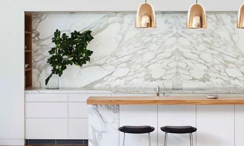On aime les suspensions imitation bronze qui s'accordent parfaitement avec la crédence en marbre clair ! Crédit photo : Pinterest/Mademoiselle Déco