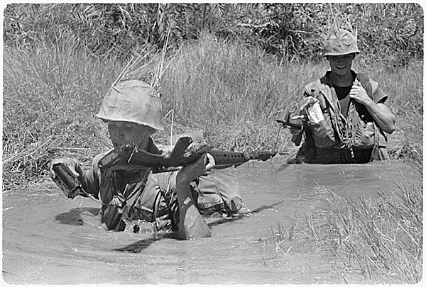 Wet going - A Marine keeps a battery pack dry as he wades through a muddy hole while on a search mission.  ARC Identifier: 532464