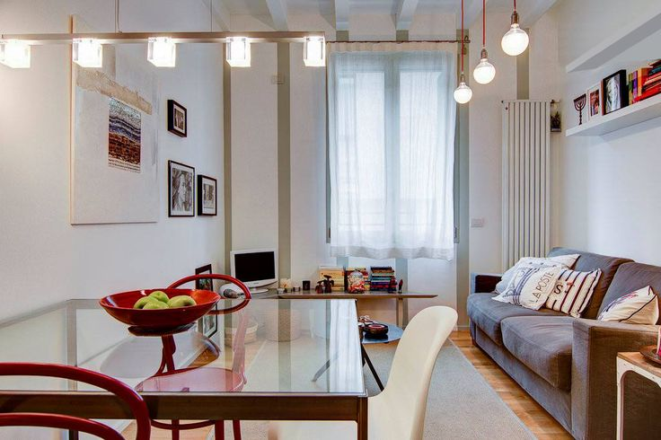 A cozy fresh apartment in central Milan by Nomade Architettura http://www.nomadearchitettura.com/#all  timber flooring, blue wall, white kitchen, panton chair, thonet chair, grey sofa, hanging lamps, iron and glass table