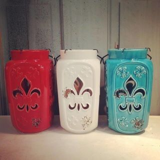 "Patio perfect!  We love these large scale ceramic lanterns with fleur de lis cut-outs on each side.  Included is a votive holder that can easily be lifted out or completely remove for a nice large pillar.  Available in three colors: red, white, blue. Measures approx. 6""x6""x11"""