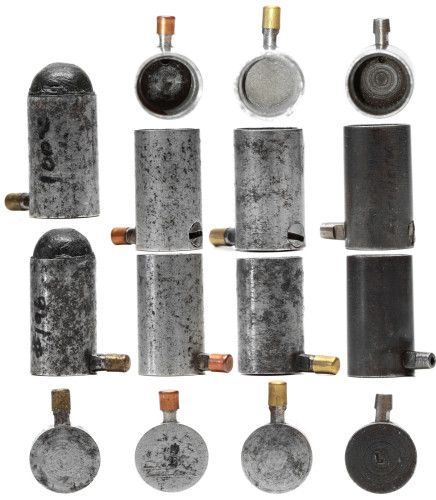 """Here are 4 variations of 12mm pinfire percussion adapters. These have a tapered """"pin"""" to allow them to fit in an unmodified 12mm pinfire revolver. The screw on the bottom of the three, unscrews to allow cleaning by pushing something all the way through from the pin.  These could be used with readily available caps and balls and powder when a supply of pinfire cartridges ran out."""
