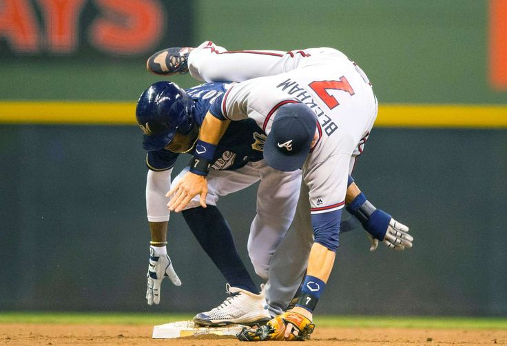 Taking a tumble:    Atlanta Braves second baseman Gordon Beckham, right, tumbles over Milwaukee Brewers center fielder Keon Broxton after reaching for a throw during the twelfth inning at Miller Park on Aug. 8 in Milwaukee. The Braves won 4-3.