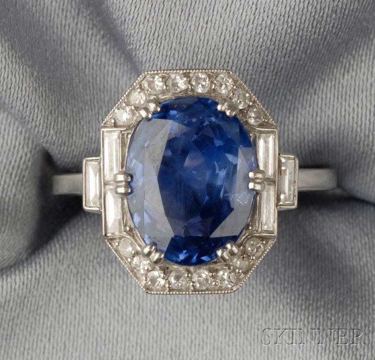 Art Deco Platinum, Sapphire, and Diamond Ring, set with an oval-cut sapphire measuring approx. 11.30 x 8.60 x 6.10 mm, framed by baguette, and single-cut diamonds, millegrain accents.