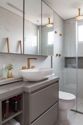 Decoração de apartamento moderno e cinza. No banheiro, lavabo, tons neutros e detalhes dourados.
