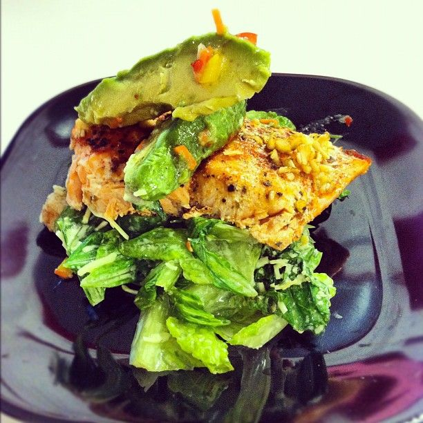 Baked garlic salmon over a spicy salad with cajun avocado slices. Follow