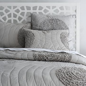 Pretty pretty - ruffled-circle quilt from West Elm. Maybe with some yellow accent pillows?