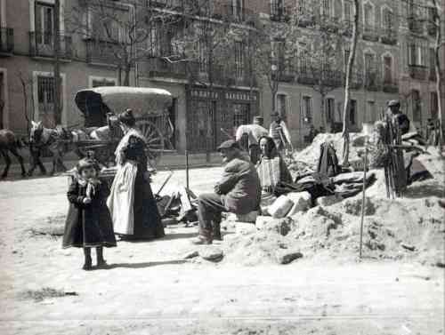 Atención a la dama ¡Qué vestimentas de diario para salir a por el pan!, ¿y la niña para jugar a las muñecas?. C/ Génova.