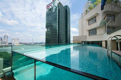 glass-walled swimming pool at Singapore's Ascott Raffles Hotel