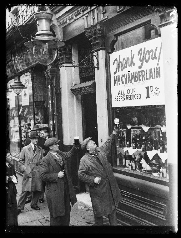 Customers outside a pub in Walworth, London, raising their glasses to celebrate cheaper beer. In his budget the previous day, Neville Chamberlain Chancellor of the Exchequer, lowered the price of beer by a penny a pint. 1933.