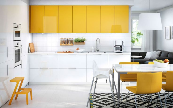 A kitchen with white and yellow doors combined with white appliances, yellow leather chairs and a white dining table.