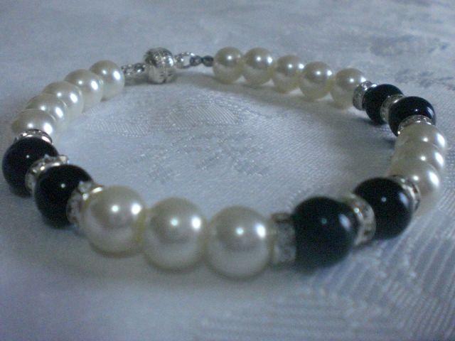 Bracciale in perle bianche e perle centrali in vetro di colore nero e rondelle argentate con strass. Chiusura magnetica argentata.Lunghezza bracciale: 20 cm.