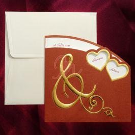 Invitatia, din carton, are imprimate elemente de design aurii pe fundal bordo. In partea dreapta sunt decupate doua inimioare aurii, prin care se vad numele mirilor. In partea stanga, sus, observam un chenar alb pe care va poate fi imprimata data nuntii. Plicul alb este inclus in pret.  #invitatie de #nunta #mirese #miri #invitatii #elegante #originale