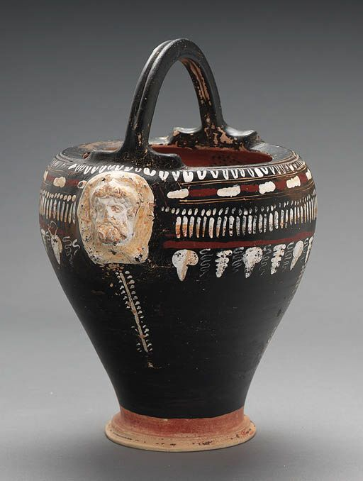 Gnatian situla, attributed to the Laurel Spray Group, 320-310 B.C.  The body decorated in white, red and yellow with stylized grape and tendril below tongue and bead bands, with mold-made masks applied to the shoulders below the arching handle, one side with Herakles with curling locks, curving mustache and full beard, the limbs knotted below his chin, the other side with a lion head spout, a strainer on the interior, 29.8 cm high including handle. Private collection