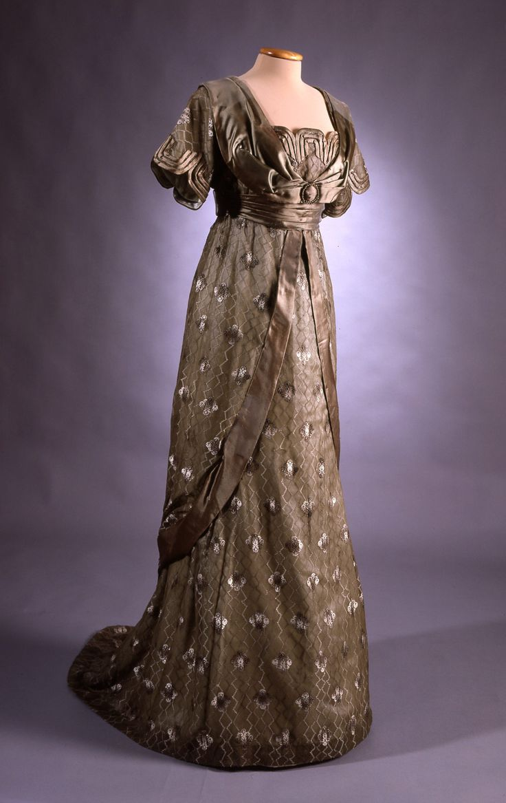 """This ballroom gown from 1912 was sewn by Ellen Helin of Helsinki. Beneath the tunic-like upper part is a dress with a train. The light-green silk lining is covered with thin silk gauze with a floral design. The gown employs as an effect the contrast of light and heavy, translucent and thick material. It also reflects the influence of the Japanese kimono. It was worn by Signe Maria Lindh, née Fabritius (born 1887) at the centennial of the Finnish Cadet Corps on October 15-16, 1912."