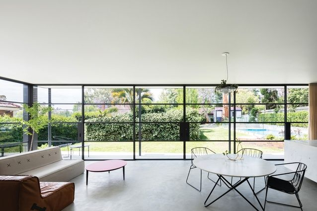 The kitchen, dining and living room look out to the garden through glass walls and sliding doors framed in fine steel.