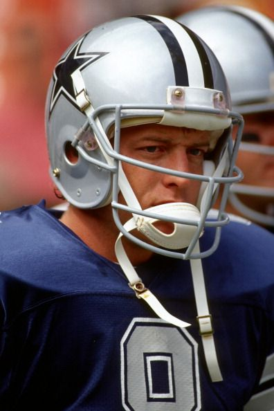 Quarterback Troy Aikman of the Dallas Cowboys looks on from the sideline during a game against the Washington Redskins at RFK Stadium circa 1990 in...