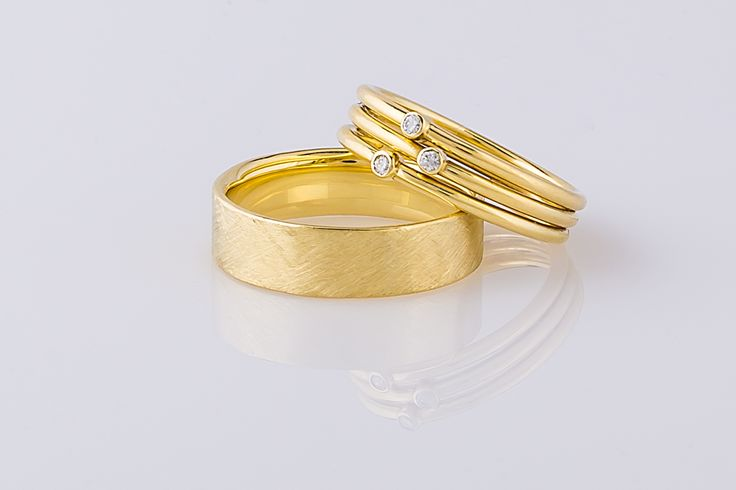 Handgemaakte trouwringen, de herenring voorzien van een bijzondere mattering en de damesring bestaande uit drie ringen met elk een diamantje.