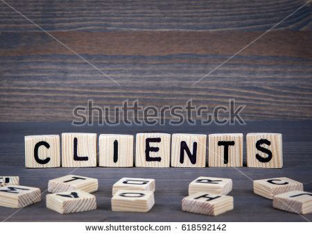 Clients word written on wood block. Dark wood background with texture.