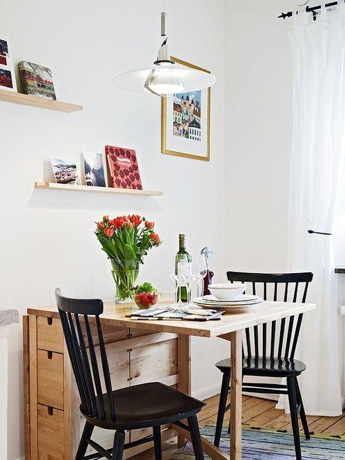 sala de jantar com mesa pequena retrátil / dobrável com pequenas prateleiras na parede