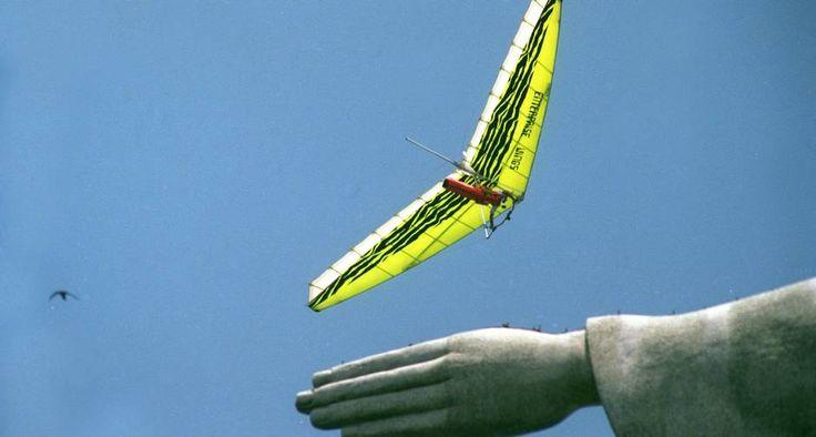 Asas. O piloto de asa-delta sobrevoa a mão da estátua, num passeio imperdível. Cristo Redentor: glo.bo/1iCK6CJ