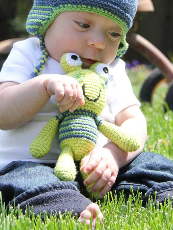 Frog Rattle from Shopping for a Change - $15.00 USD -   100% Cotton Yarns, 100% Polyester fill. Hand knitted and crocheted. Cuddly and fun. No sharp edges. Machine washable in warm water, tumble dry low setting. Meets all U.S. Consumer Product Safety Regulations.