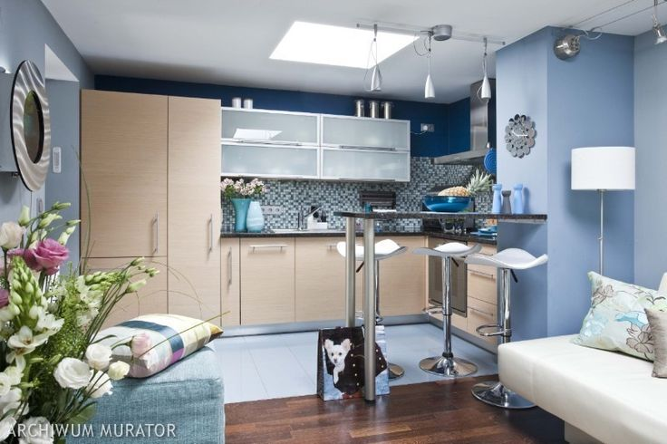 Кухня, совмещенная с гостиной. Общее освещение – большой квадратный светильник на потолке. Обеденная зона освещена светильниками, расположен...