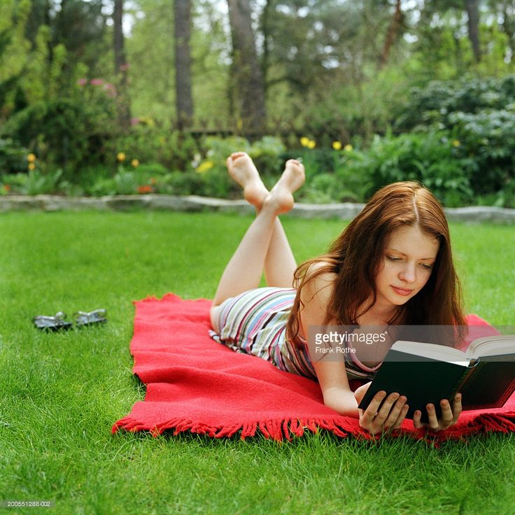 http://media.gettyimages.com/photos/young-woman-lying-on-picnic-blanket-in-lawn-reading-book-picture-id200551288-002