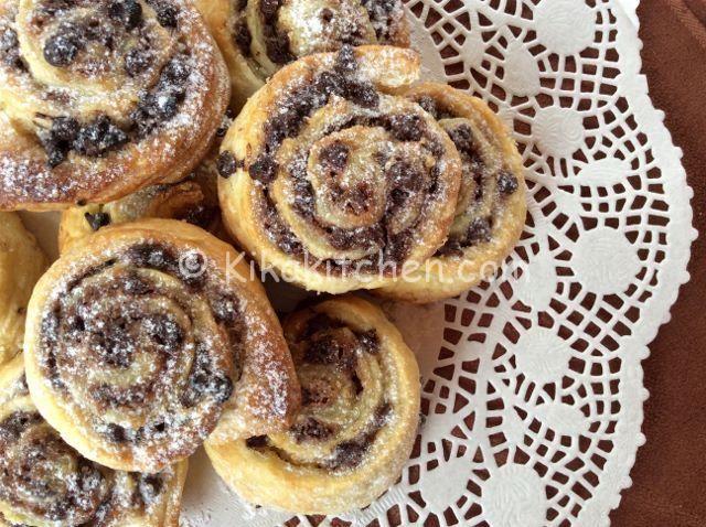Le girelle di pasta sfoglia con gocce di cioccolato sono degli sfiziosi dolcetti velocissimi da preparare. Fragrante pasta sfoglia farcita.