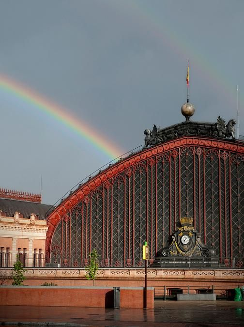 Rainbow emerging from behind the Atocha Station, Madrid, Spain
