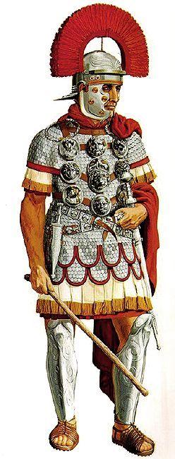 """Un centurión de la mitad del 1 er siglo (1st Century AD or 1st Century CE) usando sus decoraciones en un arnés sobre una camisa de escala. También lleva grabas protegiendo todas las espinillas desde rodilla a empeine y un casco con cresta transversal como un signo de su rango """", Peter Connolly"""