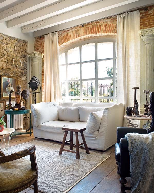 large arched window, exposed brick, beamed ceiling, exposed stone, columns, linen curtain panels and a comfy sofa. many of my favorite things.