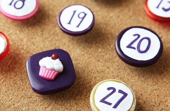 Create a corkboard calendar by adhering pushpins to numbered buttons. To see the full project, visit the article.