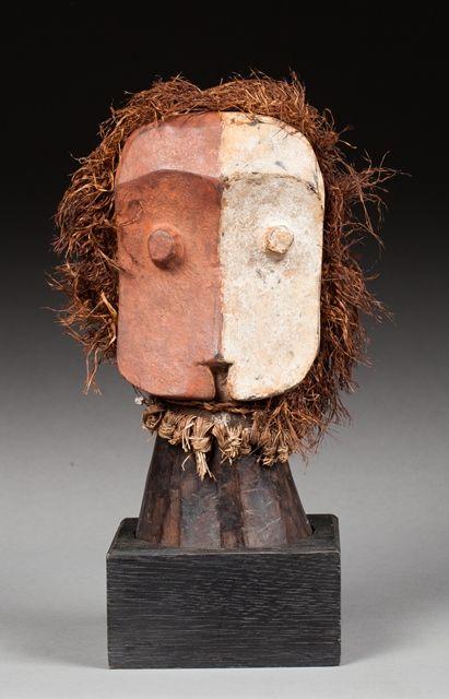 Rare fétiche Janus. Il présente un visage cubiste, les yeux sculptés en relief, l'arrête nasale discrète prenant sa source sur le front et la bouche marquée par une cavité triangulaire. Bois dur, ancienne patine d'usage brune, colorants minéraux d'origine.  Bembé, République Démocratique du Congo.  27x13x9,5cm #ArtAfricain #ArtPrimitif #AfricanArt #PrimitiveArt #Auction