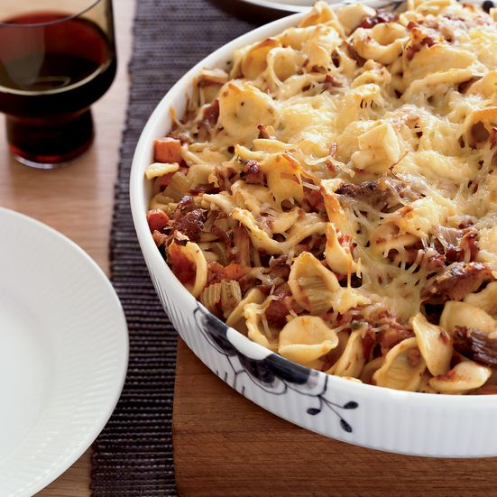 Baked orecchiette with a luscious pork sugo sauce combines braised pork shoulder, red-wine-and-tomato sauce, and a crispy topping of Parmigiano cheese.