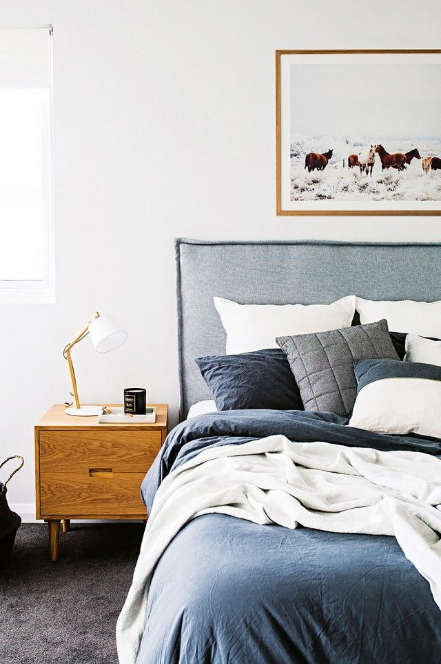 Minimal bedroom with a denim headboard, blue and white linen sheets, and a midcentury modern side table