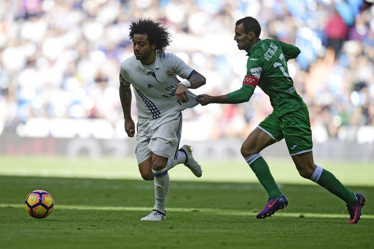 Real Madrid's Brazilian defender Marcelo vies with Leganes's defender Diego Rico during the Spanish league football match Real Madrid CF vs Club Deportivo Leganes SAD at the Santiago Bernabeu stadium in Madrid on November 6, 2016.