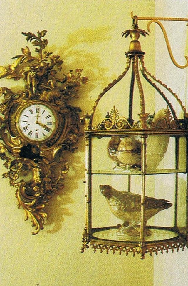 Switzerland residence. This photo is from a 25 year old magazine. An 18th century clock by Baillon… still keeping time with its original movement. And lantern with 18th century Strasbourg faience birds….House and Garden Dec. 85 Trouvais