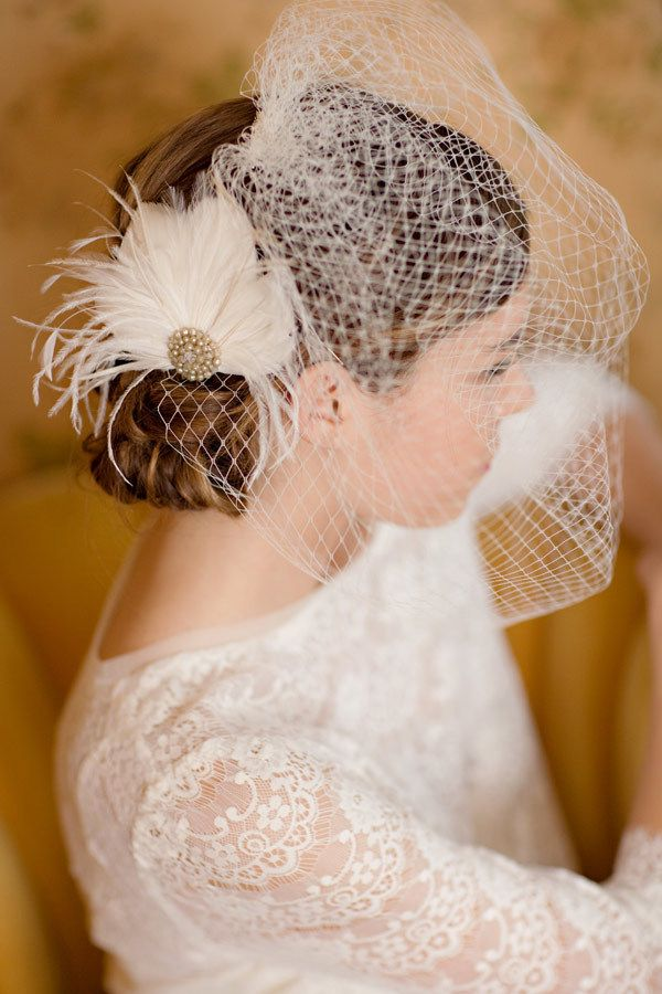 Feather hair fascinator made of goose, ostrich, and stripped coque feathers and centered with a vintage pearl earring. Veil in picture sold separately.