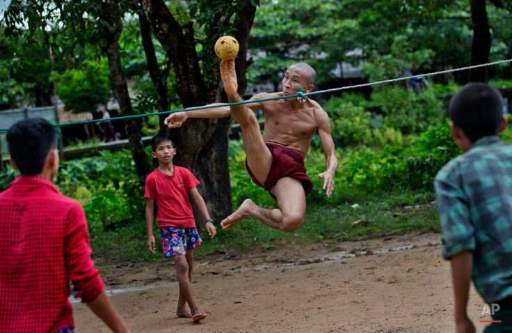 In this Sunday, Sept. 29, 2013 photo, an airborne Buddhist monk kicks a rattan ball during a game of Chinlone in Kawhmu, Myanmar, southwest of Yangon. A combination of sport and dance, it is played between two teams of six players each, passing the ball back and forth with their feet, knees or heads. (AP Photo/Gemunu Amarasinghe)